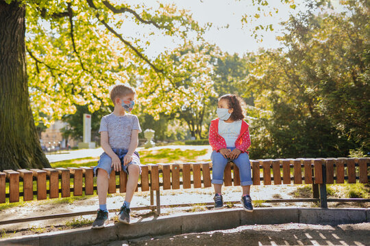 Cute little boy and small girl in summer sunny day, wearing protective mask in social distancing sitting on bench in park. Full body portrait.