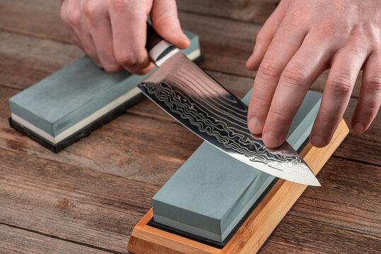 Man sharpens a Gyuto knife using a whetstone