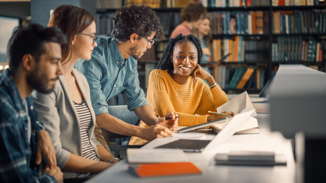 University Library: Diverse Group of Gifted Students Have Discussion, use Laptop, Prepare for Exams Together, Helping, Researching Subjects for Paper Assignment. Happy Young People Study for Future