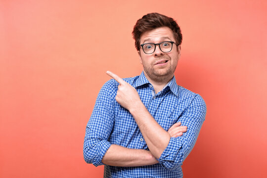Confused puzzled man in glasses and blue shirt pointing finger aside