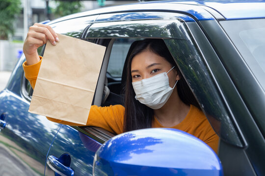 Asian woman wearing mask and holding paper bag of fast food through the window car. Drive thru food service concept