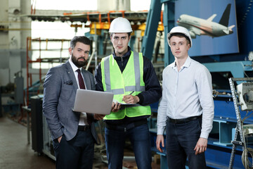Portrait of a 3 men in a airplane manufactory. Two company managers and one factory worker deciding future plans. Business solution.