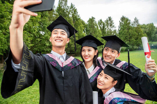 Four college students wearing bachelor's clothing using a mobile phone