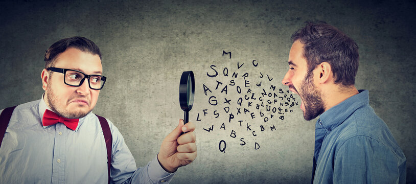 Curious businessman looking through a magnifying glass at an angry screaming man