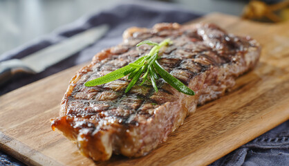 grilled new york strip steak resting on wooden cutting board with rosemary garnish