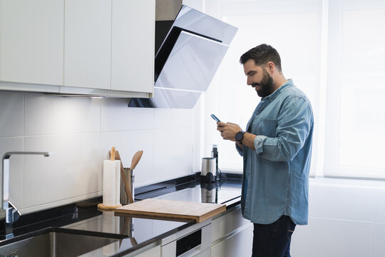 Man cooking crepes in the kitchen with a mobile phone in a denim shirt