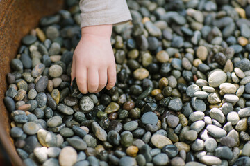 Toddler hand picking up small stones