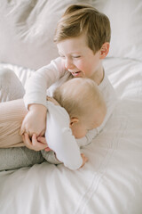 Toddler boy and baby sister playing on bed at home