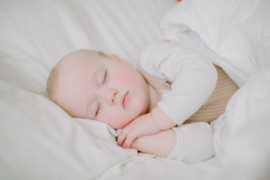 Baby girl sleeping peacefully in white bed facing camera with hands fo