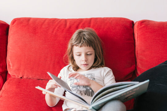 Girl reading a story on the couch