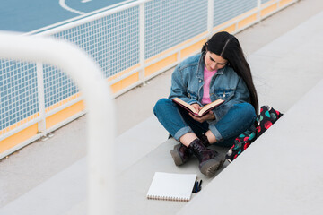 Young university student reads and takes notes on campus