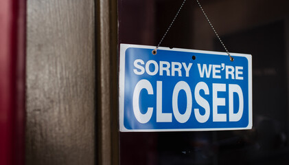 Close up of a closed sign hanging in the window of a store.