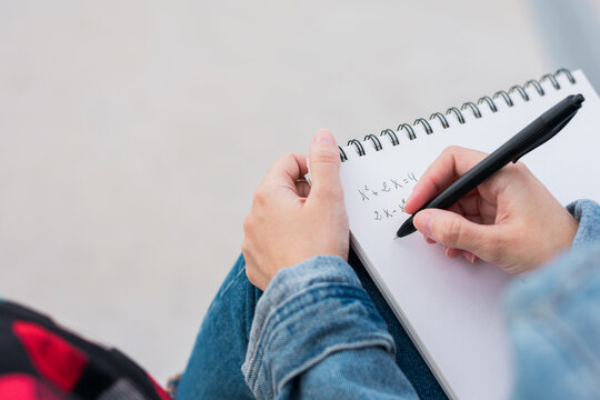 Close up of a young college student taking notes on campus