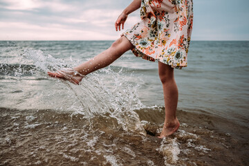 young girl in dress splashing water in lake Michigan