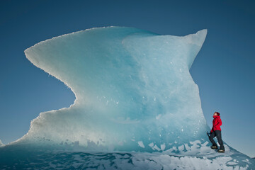 Woman climbinbg iceberg on the Fjallsjoull glacier lagoon