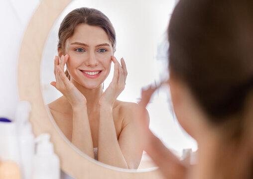 Beautiful woman looking at mirror and applying eye serum