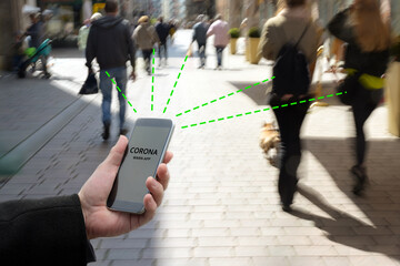 Photo Blinds London Smart phone with Corona Warn App, the contact tracking or tracing application against Covid 19 pandemic is connecting phones from moving people in the city to analyze the risk of infection
