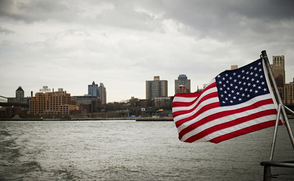 National flag of USA waving on pole of floating vessel against cloudy sky near New York City coast