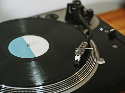 From above contemporary vinyl record player with retro disc placed on wooden table in living room