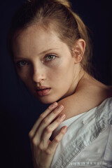 Young lady in white shirt touching delicate skin of shoulder and looking at camera on black background