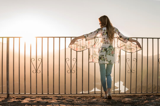 Back view of female tourist in casual clothes standing near metal fence and admiring sundown view during walk on summer day