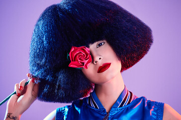 Crop female model in synthetic wig and with red lipstick in a purple background holding a rose