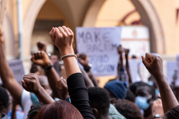 People raising fist with unfocused background in a pacifist protest against racism demanding justice
