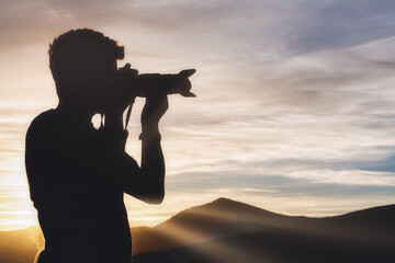 Side view of young male traveler in silhouette standing on hill and taking picture of spectacular scenery of mountain range on sunset