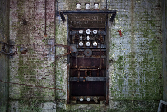 Old broken rusty mechanism with worn steel pipes of coils and rods in dilapidated gray brick wall covered with moss in abandoned factory
