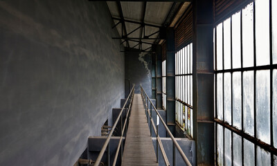 Narrow wooden bridge with steel handrails locating above rooms with gray concrete walls and dusty dirty large windows inside abandoned factory