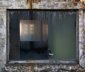 Fragment of weathered stone wall with small dirty window of derelict industrial building