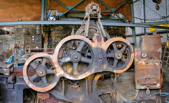 Old used rusty mechanism made of steel discs of various diameters mounted on metal device in dirty abandoned factory building