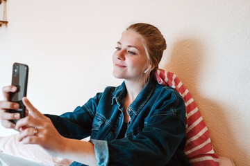 Joyful young female in wireless earphones and denim jacket smiling at screen and taking selfie with smartphone while relaxing on bed in modern apartment