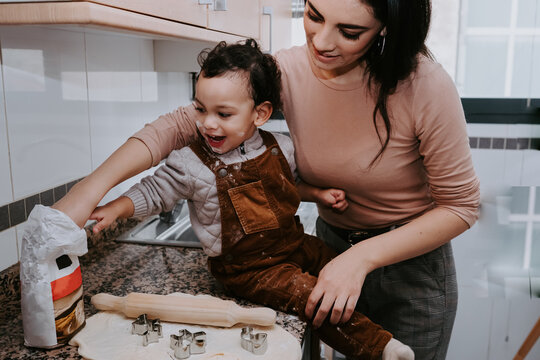 Side view of cheerful young mother in casual clothes preparing dough with rolling pin with son standing on chair in light kitchen