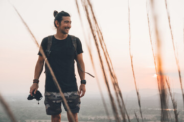 Young cheerful male traveler in casual clothes with photo camera standing on edge of cliff and taking picture of majestic landscape of green forest during sunset