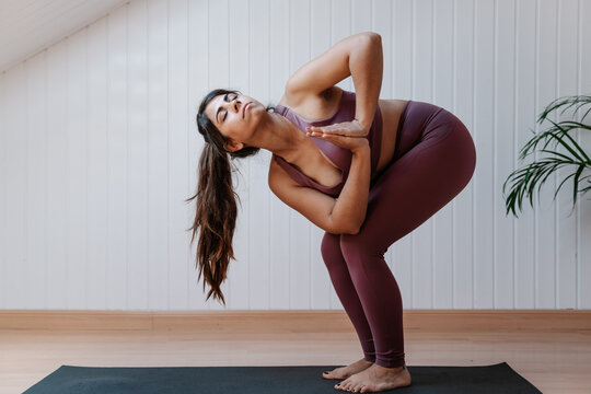 Side view of young female in sportswear standing in Revolved Chair Pose or Parivritta Utkatasana while practicing yoga in studio