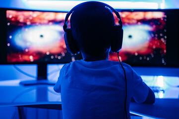 Back view of unrecognizable male kid in headphones watching film about planets on desktop computer while sitting at table in room with blue light