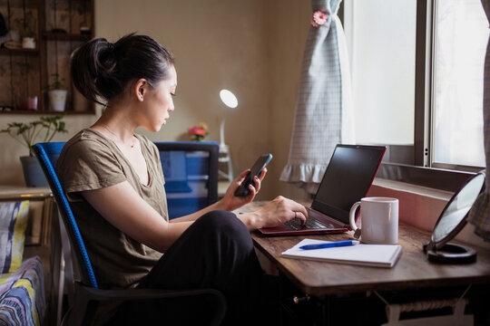 Side view of Asian female freelancer in casual t shirt sitting at table and browsing computer working on project online at home while texting on the smartphone