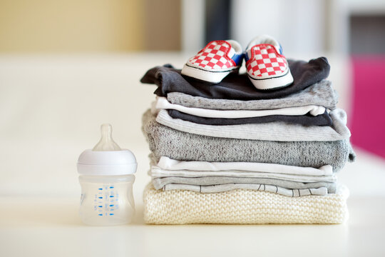 A pile of baby clothes, feeding bottle and little newborn shoes. Parenting expenses concept. Working out a baby budget. Saving money when planning for a newborn.