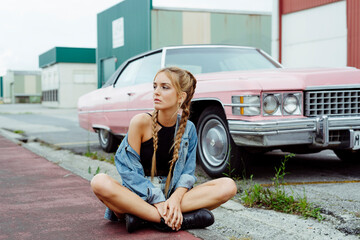 Attractive blonde girl sitting on the sidewalk near to a classic pink car