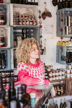 Friendly adult woman with curly hair leaning on shelf and looking away while working in cozy local delicatessen food shop