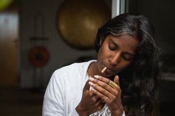 Young Indian female in casual clothing standing with closed eyes on terrace and smoking marijuana roll up while relaxing