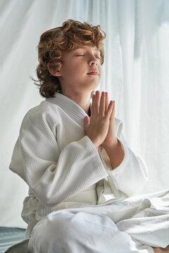 Thoughtful young boy in white kimono sitting with legs crossed and hands together while practicing meditation with closed eyes during training judo at home
