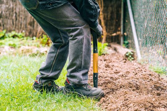 Unrecognizable farmer digging soil with shovel in garden