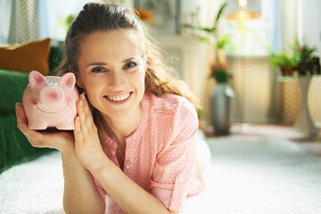 smiling woman with piggy bank in modern house in sunny day