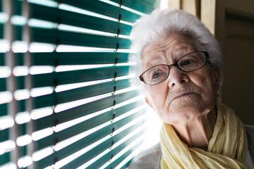 Elderly woman standing near window during pandemic