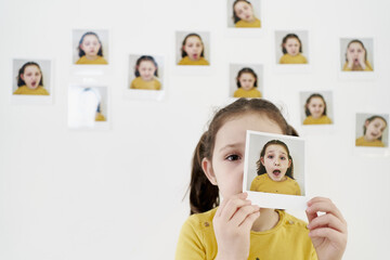 Cute little girl in yellow dress hiding face behind own picture while standing against wall with photos demonstrating various emotions