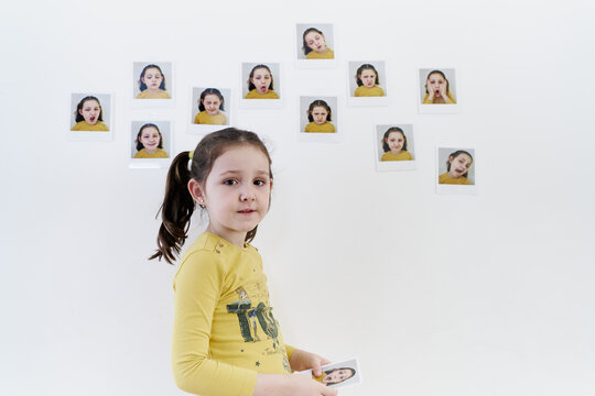 A cute little girl in a yellow t-shirt looks at a picture of her next to a white wall with other pictures of her emotions attached