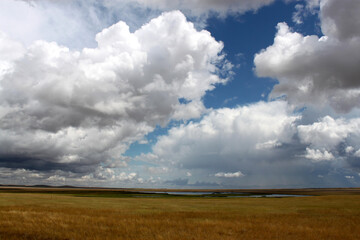 Poster Taupe Dynamic cloudy blue skies over grassy fields and calm water in central Montana