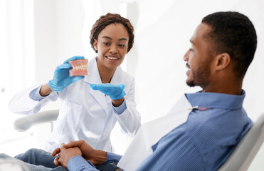 Female dentist showing male patient plastic model of human jaw